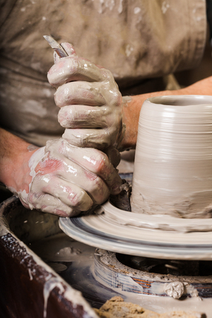 the process of creating a pottery on a twisted Potters wheel close-up. Dirty hands in the clay and the potters wheel with the workpiece.