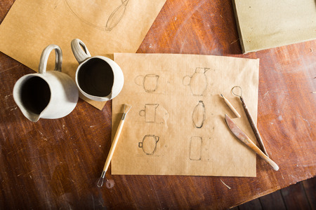 flat lay of clay pitchers, sketching of jugs made on Kraft paper and tools for working with clay, handcrafted work. Reklamní fotografie