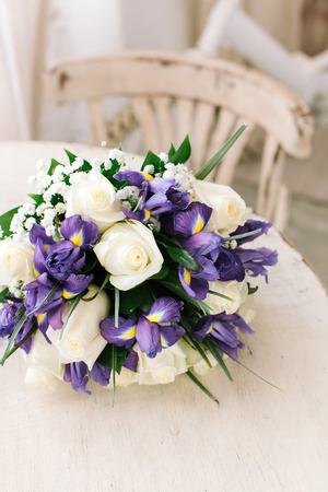 beautiful wedding bouquet of fresh violet irises and white roses on a white table. Фото со стока