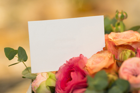 flower arrangement, present concept. close up of empty white card in bouquet of flowers.