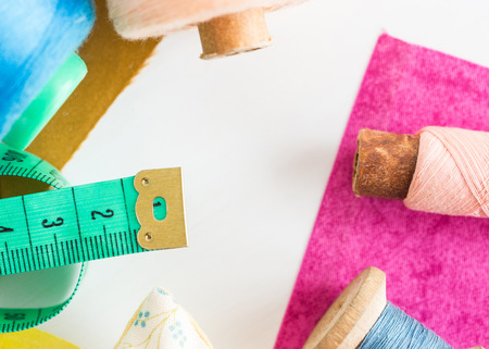 patchwork, sewing and tailoring concept - close-up on tools, measuring meter, blue and pink threads in bobbins and purple and mustard color patches on white background, top view, flat lay.