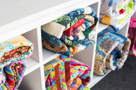 patchwork, sewing and fashion concept - colorful finished quilts in the studio at white shelves with few storage compartments, the warehouse of finished products, side view, selective focus. Фото со стока