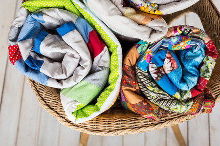 patchwork and fashion concept - close-up on three colorful quilts rolled into a tube and laid in a wicker chair, warehousing of finished products on a white background, top view