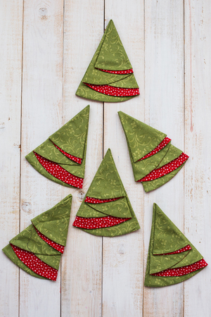 patchwork and quilting concept - macro of colorful decorative red-and-green napkins on a whitewashed wooden floor, festive embroidered towels in shape of Christmas trees, top view, flat lay, vertical.