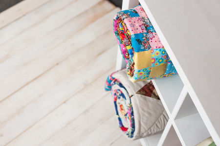 patchwork, sewing and fashion concept - two colorful quilted blankets at white shelves with few storage compartments in studio, white floor in warehouse of finished products, top view. Фото со стока