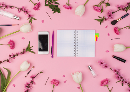 business lady, office, planning concept. top view of the pink background are laying mobile phone, small clean planner, fresh flowers and woman's cosmetics and accessories. Archivio Fotografico