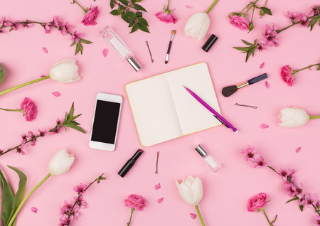 business lady, office, planning concept. flat lay, on the pink background are laying mobile phone, small clean planner, fresh flowers and womans cosmetics and accessories.