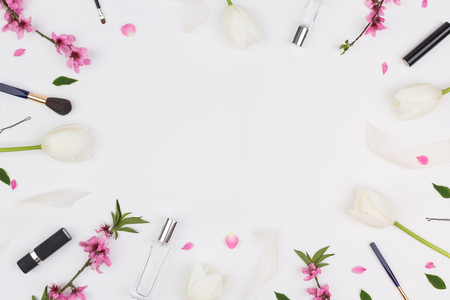 backdrop, calmness, women day concept. adorable background of white colour with fresh flowers and womans cosmetics on it, which placing on the edges and creat a frame, surrounding leaves and petals. Flat lay