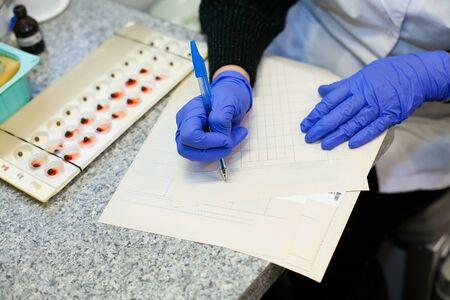 Doctors hands fill in different tables and forms during working process of blood tests. 版權商用圖片