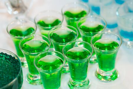 Green molecular caviar cocktails filled with glasses.