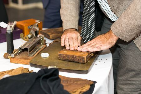 The moment of making an extra class cigar with the help of traditional Cuban production tools. measuring the length and thickness of the cigar with the help of cepo