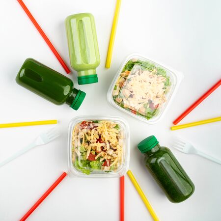 Business and food. A set of healthy food for a take-away working lunch. Green smoothies, and salads on a white background. The concept of delicious lunches.