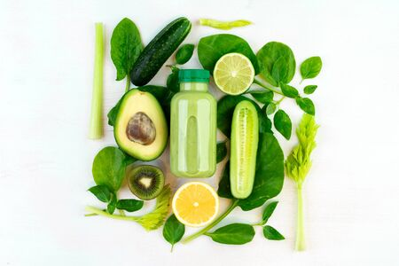 Set of fresh vegetables to make a green smoothie detox on white backgorund. Fllat lay, top view. Fresh drink for proper nutrition in a bottle Imagens