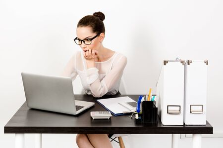 Suprised young businesswoman wearing eyewear working on laptop in white modern office. The concept of distance education or working from home in quarantine. Unemployment, the fall of stock indices, shocking news. Imagens
