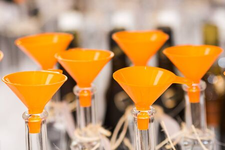 Close-up of the orange funnels embedded in empty liquid bottles. Alcohol container filling.