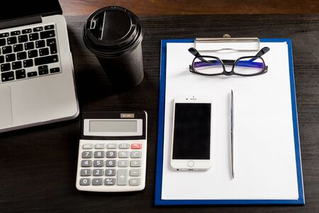 Items for business and accounting in the composition in the office on the table. Working from home setup. Laptop, cell phone, calculator, eyewear, pen, clipboard with blank white paper sheet and coffee on wooden rustic desk. remote working or studying. Working space at home. top view. Archivio Fotografico