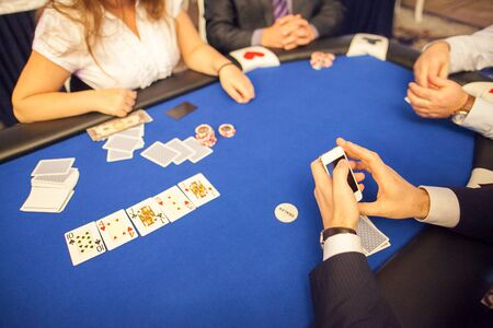 A group of people, gambling players sitting at a poker card game table. Focus on mans hands with smartphone. Stockfoto