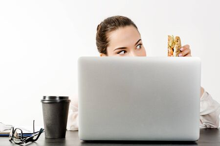 A young woman sitting at a table on a white background behind a laptop holds a sandwich in her hand and looks at it with hungry greed. The concept of office life and business lunch