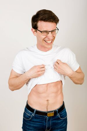 Young sexy guy with glasses stands on a white background and laughs as he lifts up his shirt showing his pumping press.