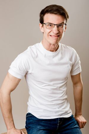 A young, muscular guy wearing glasses, a T-shirt and jeans sits on a gray background and makes fun of himself looking at the camera.