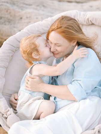 lifestyle concept. wonderful little red haired girl kissing and hugging her mother with same colour of hairs, dressed in cotton shirt and skirt Imagens