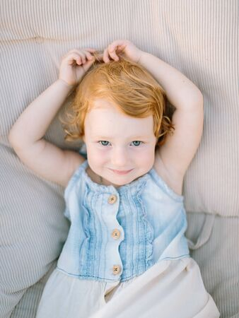 portrait of extremely cute little girl with pale skin, curly red hair and charming green eyes, she is dressed in denim sundress Archivio Fotografico