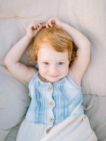 portrait d'une petite fille extrêmement mignonne à la peau pâle, aux cheveux roux bouclés et aux yeux verts charmants, elle est vêtue d'une robe d'été en jean Banque d'images
