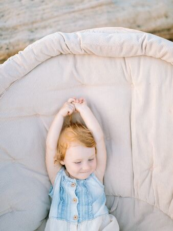 lovely red haired child wearing small beautiful sundress, she is sitting in the big armchair, stretching her hands up and smiling