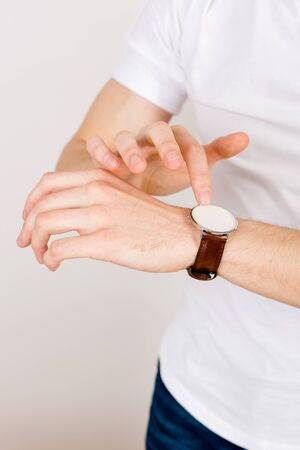 Cropped vertical frame - hands on a white background interact with the touchscreen of a wrist watch. The concept of working with augmented reality.