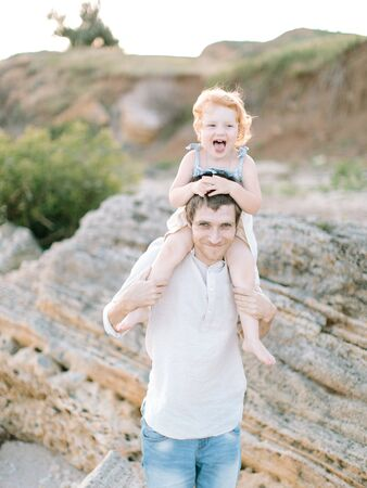 family concept. young handsome smiling man holding on his shoulder small sunny red haired child Imagens