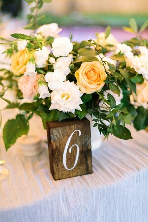 A close up of the festive, wedding table. A wooden plate with a number and a flower centerpiece of white and yellow roses and greens. Vertical frame