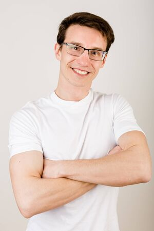Crop portrait of a trustworthy young man standing with his hands crossed on his chest and smiling straight into the camera against a white background.