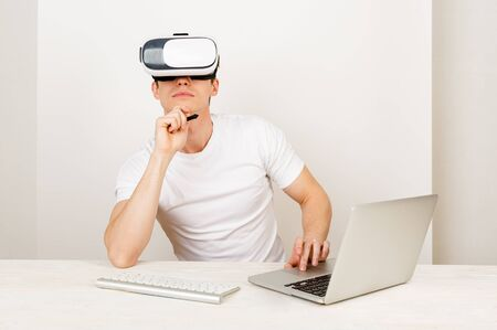 Young man employee using virtual reality headset interacts with augmented things orienting in three dimensional space while sitting on his desk with keyboard and laptop on white background.