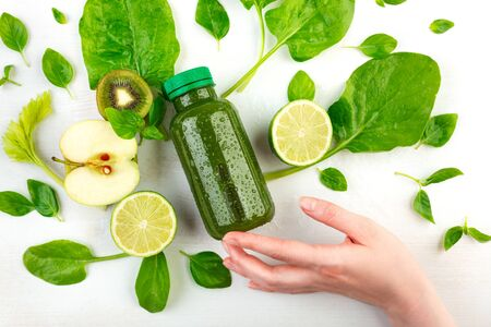 A woman's hand holds at her fingertips a bottle of green detox, wich is surrounded by fresh fruits, vegetables and leafs. The glorification of a healthy vegetarian diet conception. Imagens