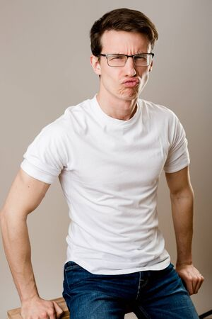 A young, muscular guy wearing glasses, a T-shirt and jeans sits on a gray background and fool around looking at the camera.