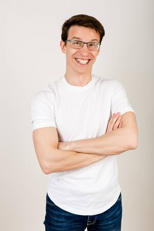 A young hipster in casual clothes stands on a white background with his hands folded on his chest and laughs heavily, looking straight into the camera.