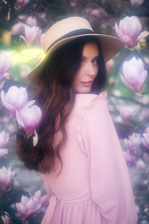 Soft focus. Charming tender woman in delicate dress and hat looking at camera walking in blooming magnolia garden Imagens