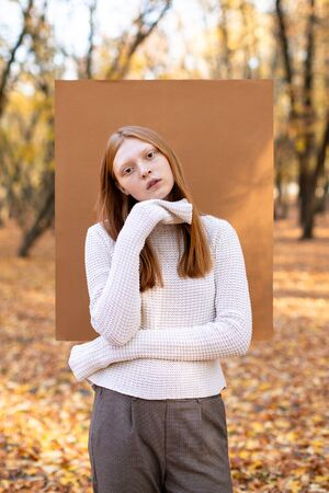 Female model in trousers and white loose long-sleeve sweater standing against carton square in autumn forest