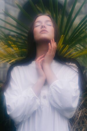 Soft focus. Tender calm woman with long hair and in white shirt folding hands and raising face up with closed eyes on background of greenery