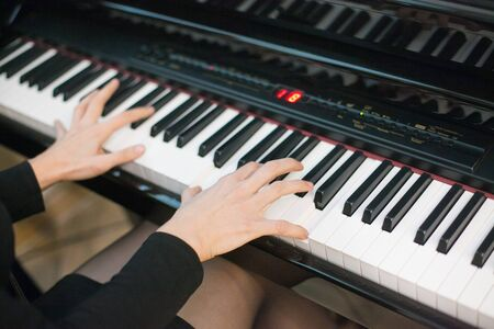 From above crop of hands playing on piano.