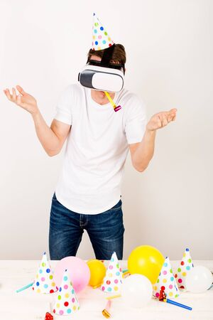 a guy wearing glasses is blowing into a party whistle and raising his hands in a misunderstanding gesture standing in front of a festive table . The concept of no pleasure in online communication