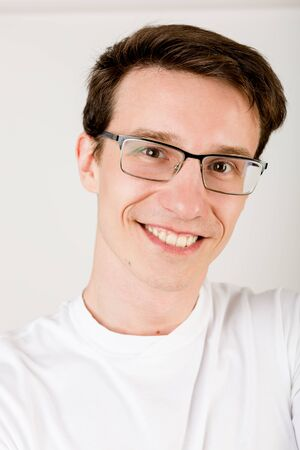 Young smiley guy with dark hair, glasses and a T-shirt making selfies on a white background.