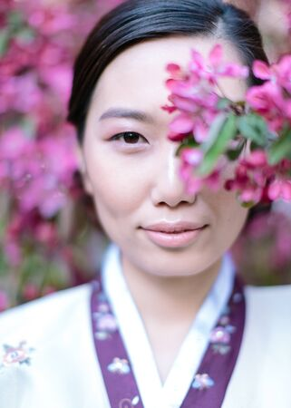 Asian beauty. portrait of young and beautiful korean woman that is hiding among branches of the tree with sakura pink flowers.