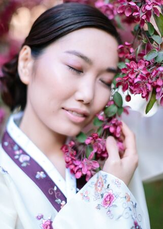asian culture concept. on the bright background of tree in red flowers there is charming asian woman with closed eyes holding branches of the tree