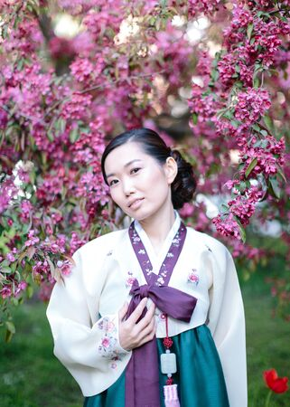 Asian spring. Adorable korean woman wearing traditional clothes hanbok, asian young woman standing among flowering trees in the garden. Imagens