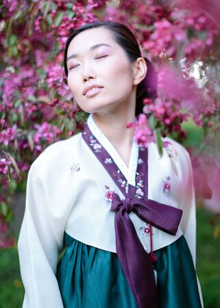 Concept of asian beauty. Portrait of marvelous korean woman with closed eyes and smile, asian girl wearing silk hanbok and standing nearby with sakura tree tree
