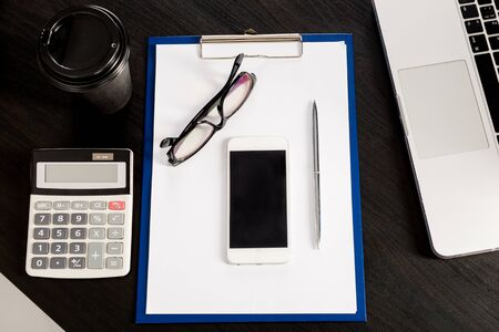 flat lay composition with laptop, pen, coffee, cell phone, calculator, eyewear, clipboard with blank white paper sheet on dark background. Analysing Statistics, Financial Concept. Office table, accountant's desk. Archivio Fotografico