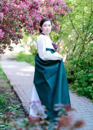 Natural portrait of beautiful young Korean girl standing in the middle of a blossoming spring garden, holding the hem of a traditional Korean dress with her hand and posing on camera.