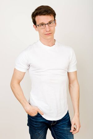 An attractive guy in casual clothes stands on a white background with his hand in his pocket and looks into the camera, lightly thoughtfully, yet calmly and confidently.