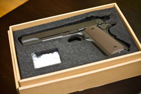 Strikeball pistol with bb bullets in a cardboard box on a glossy black desk. Concept of weapon presentations and selling.